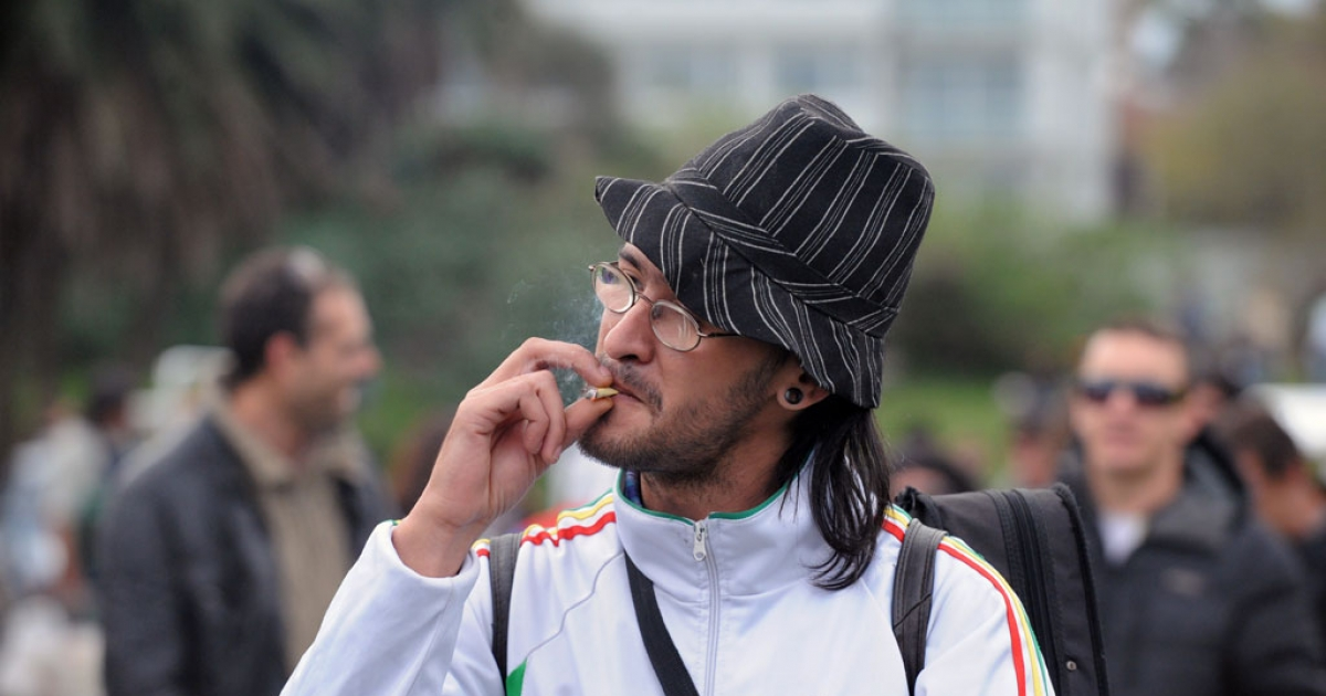 A man smokes marijuana during the World Day for the Legalization of Marijuana on May 3, 2014 in Montevideo.</p>