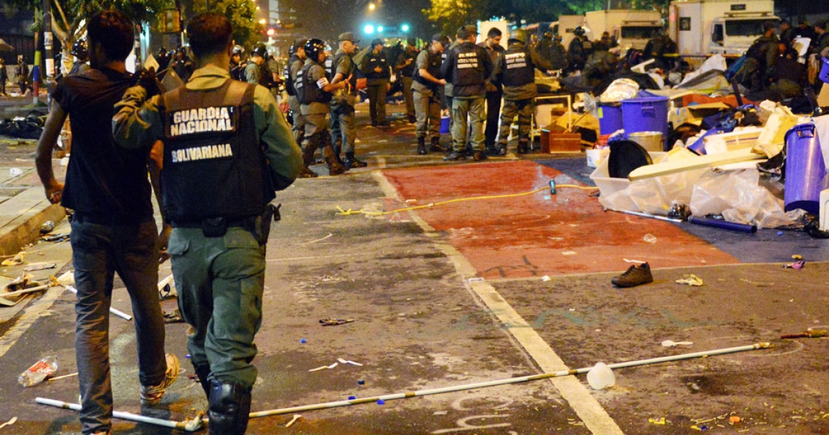 A student is taken into custody as National Guard personnel in riot gear dismantle a students' encampment set up in front of the UN headquarters in Caracas on May, 8, 2014.</p>