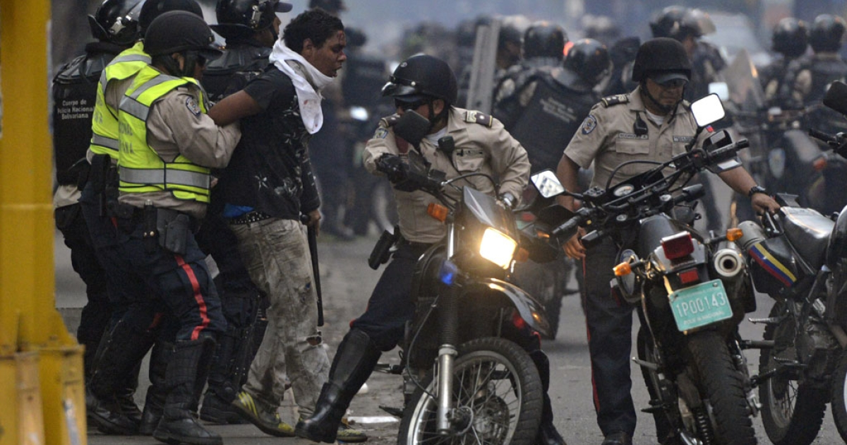 An anti-government activist is arrested by national police during a protest against Venezuela President Nicolas Maduro government in Caracas on March 13, 2014.</p>