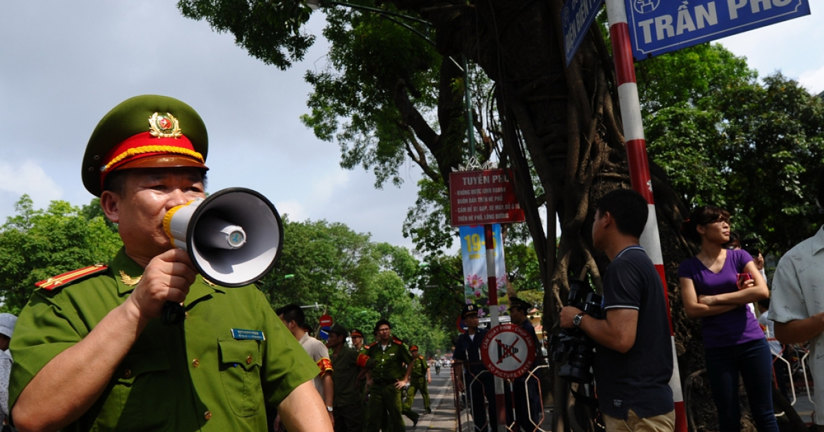 Policemen ask people to leave  a street near to the Chinese embassy in Hanoi on May 18, 2014.</p>