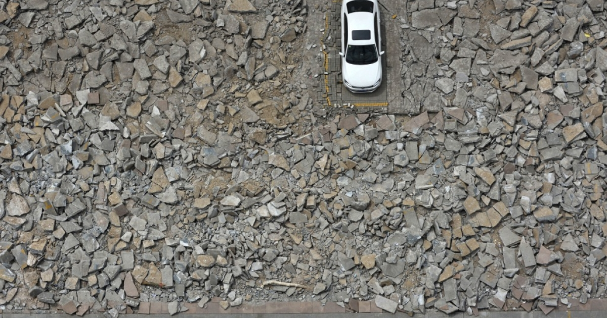 A car that was left behind in a shutdown carpark is surrounded by debris after construction began to widen a street in Taiyuan in China's Shanxi province on May 6, 2013. The construction unit started working around the car for several days after they failed to contact the owner.</p>