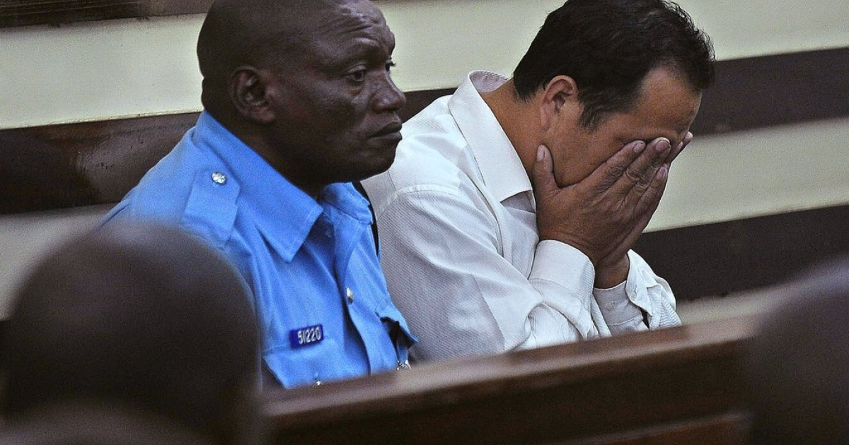 Tang Yong Jian (R), 40, a Chinese national, buries his face in his palms after he was arraigned in a Nairobi court January 27, 2014 for trying to smuggle 3.4 kg of raw elephant ivory through Kenya on transit to Guangzhou, China from Mozambique.</p>