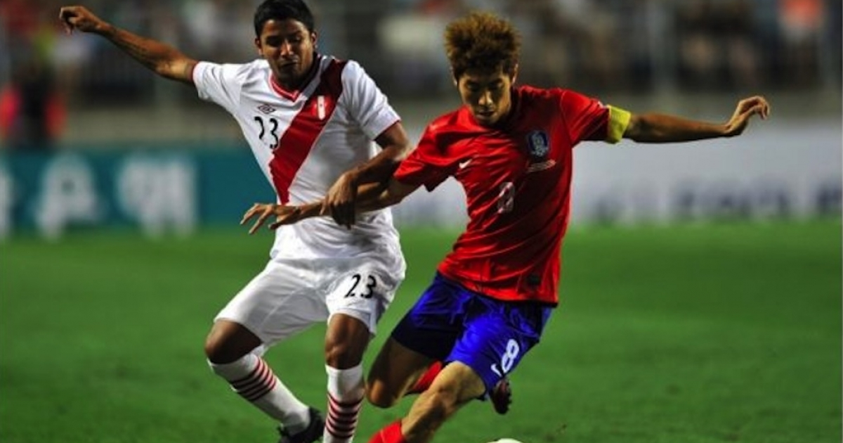 Peru's Reimond Manco, left, vies for the ball with South Korea's Ha Dae-Sung during a friendly soccer game on Aug. 14, 2013.</p>