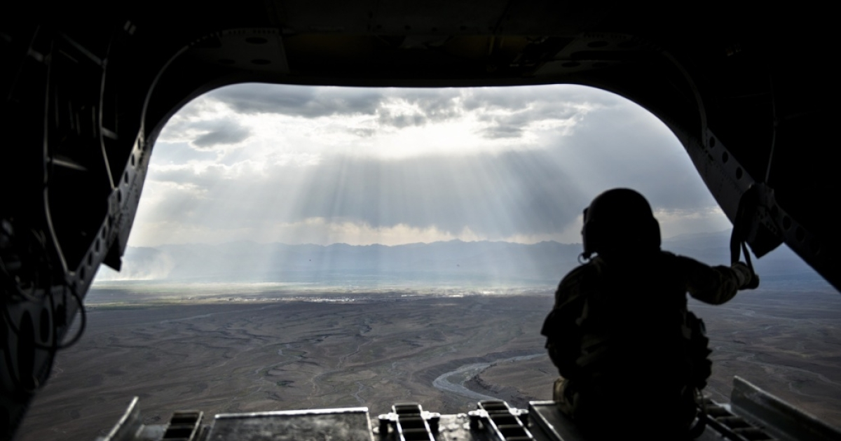 A US soldier looks at a mountain range in Afghanistan's Logar Province from a US Chinook helicopter on May 28, 2014.</p>