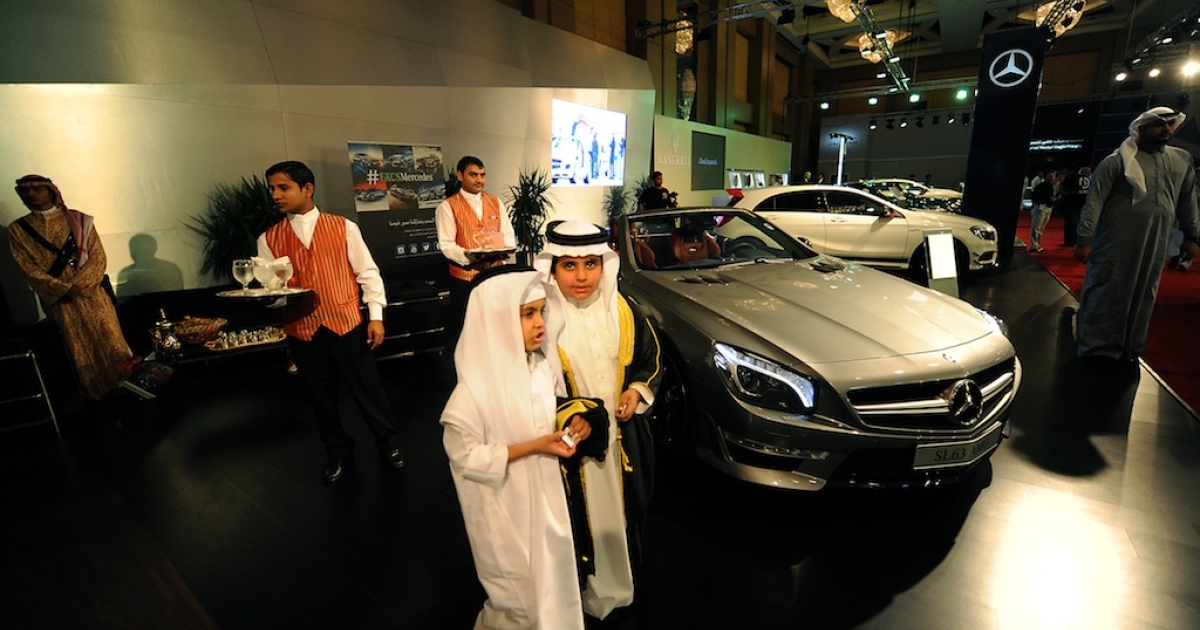 Saudi boys walk past luxury Mercedes cars displayed at the 2013 International Luxury Motor Show in the capital Riyadh on October 29, 2013.</p>