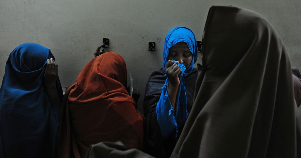Women hide their faces as they wait in line to be vetted at a temporary center on April 9, 2014 in Nairobi, Kenya. Officials said dozens of Somalis have been expelled from Kenya.</p>