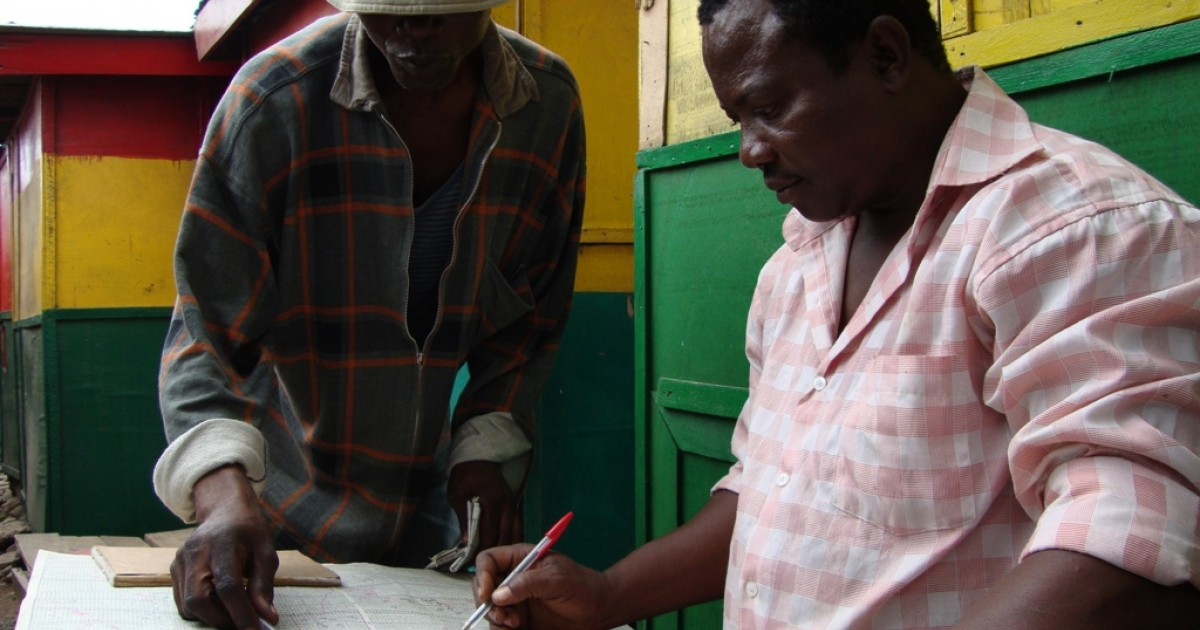 Ghanaian lottery forecaster William Galley, right, consults extensive charts to make a prediction about what will be the lucky numbers in the next day's lotto. Many who bet on the national lottery seek the advice of forecasters like Galley, and if they win they return to pay them