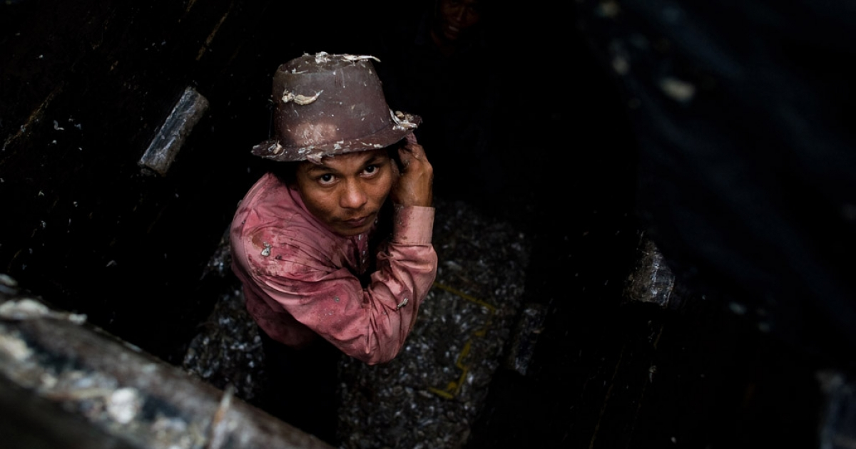 A migrant laborer at work on a Thai fishing boat in Sattahip, Thailand's Rayong province, Sept. 1, 2011.</p>