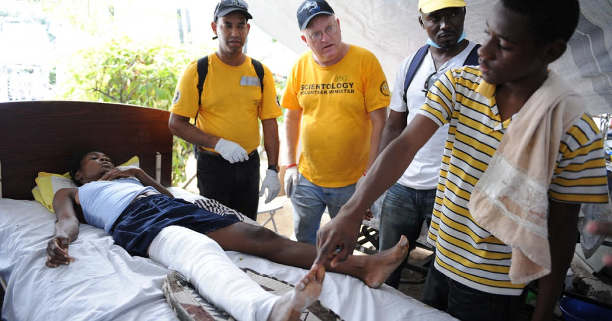 Scientologists Dave McGregor (second from the left) and Ricardo Garcia (left) teach a relative of a patient their touch healing treatment method at a hospital in Port-au-Prince on Jan. 26, 2010.</p>