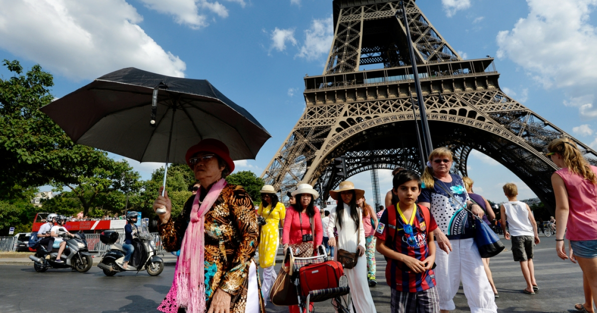 Tourists walk in front of the Eiffel Tower in Paris on July 19, 2013.</p>