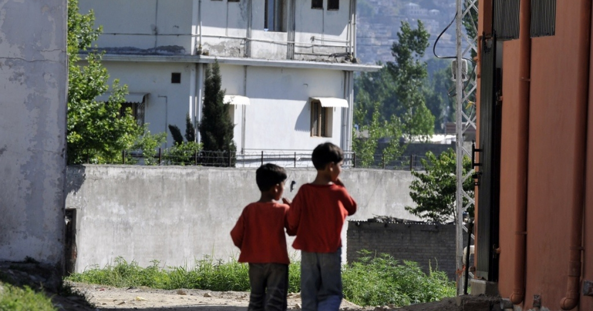 Pakistani boys walk toward Osama Bin Laden's final hideout as military and police keep the area cordoned off in the Bilal Town neighborhood of Abbottabad on May 8, 2011.</p>