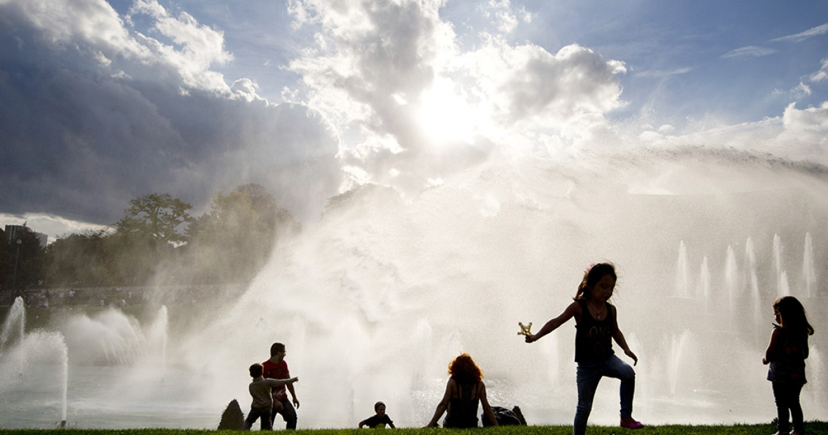 People and children enjoy sunbathing and refreshing by the Trocadero fountains on Oct.19, 2014 in Paris.</p>