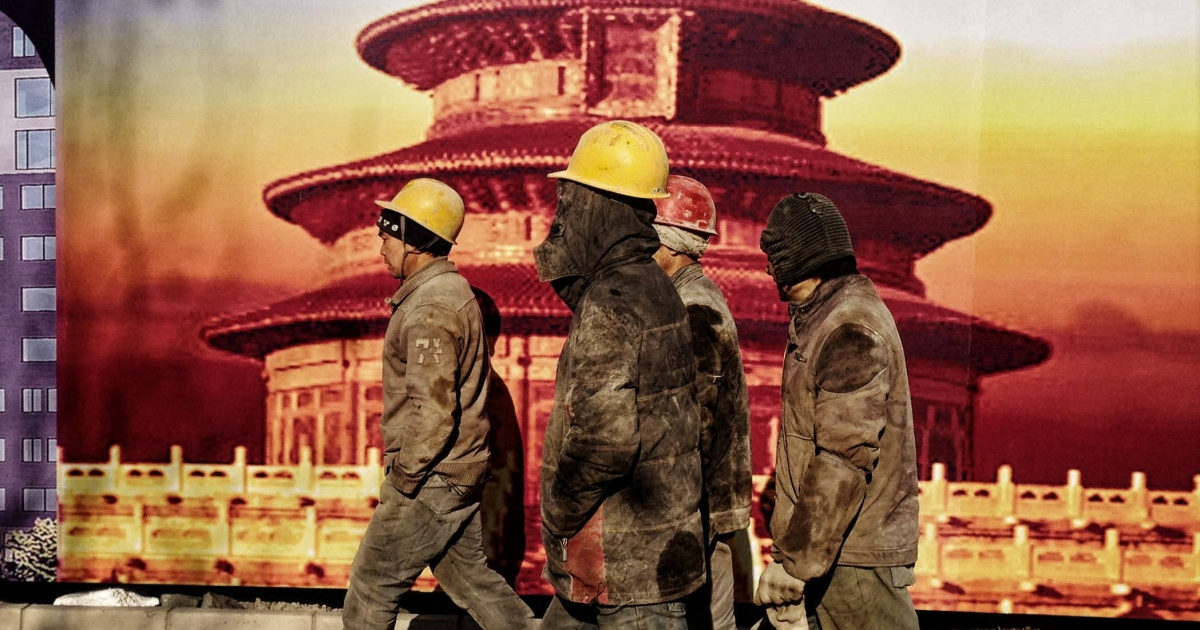 Migrant workers who do construction in Beijing walk by a banner showing the Temple of Heaven, a landmark in Beijing. Beijing, a sprawling metropolis, has a growing so-called