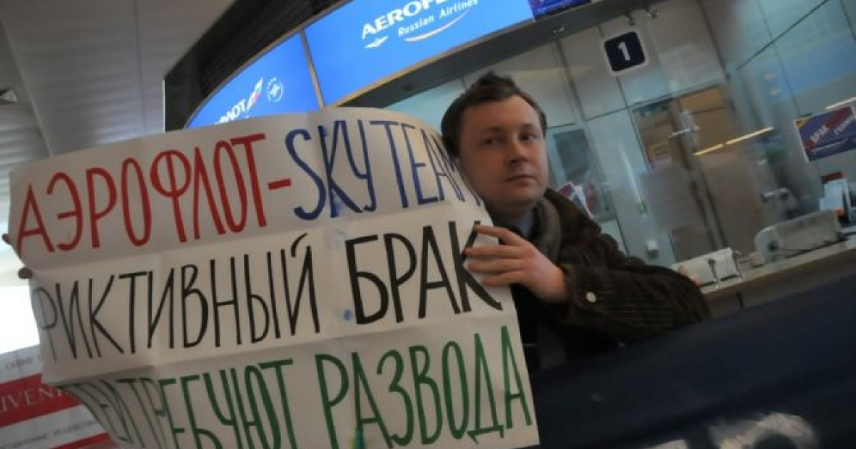 Gay Russian activist Nikolai Alekseyev holds a poster that reads