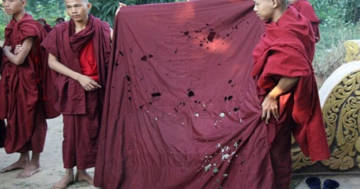 Monks show robes burned in a Nov. 29 attack on protesters. Police razed sit-in camps where monks were sleeping, injuring numerous people.</p>