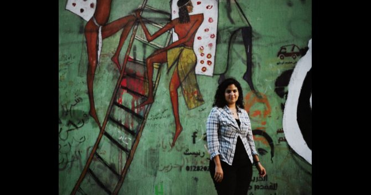 Mariam Kirollos, an activist, stands in front of murals on Mohamed Mahmoud Street, just outside Tahrir Square in Cairo in May 2012.</p>