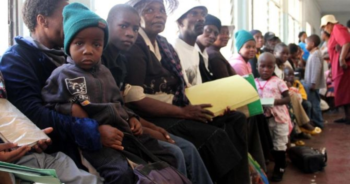 Zimbabweans wait in line at Mpilo Hospital in Bulaweyo to collect monthly allocations of antiretroviral drugs (ARVs).</p>