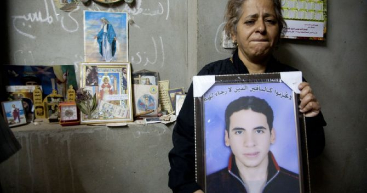 Evon Loga Gabrieul holds a portrait of her deceased son Ayman Nabil Labib, who was beaten to death by classmates on Oct. 16, at her family home in Mellawi, Egypt.</p>