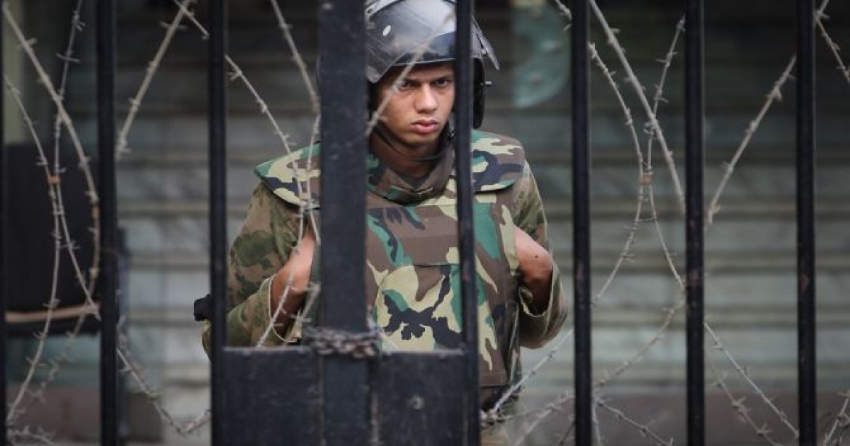 A soldier watches as protestors stage a sit-in outside the government cabinet office on November 26, 2011 in Cairo, Egypt. Thousands of Egyptians are continuing to occupy Tahrir Square ahead of parliamentary elections to be held on November 28. </p>