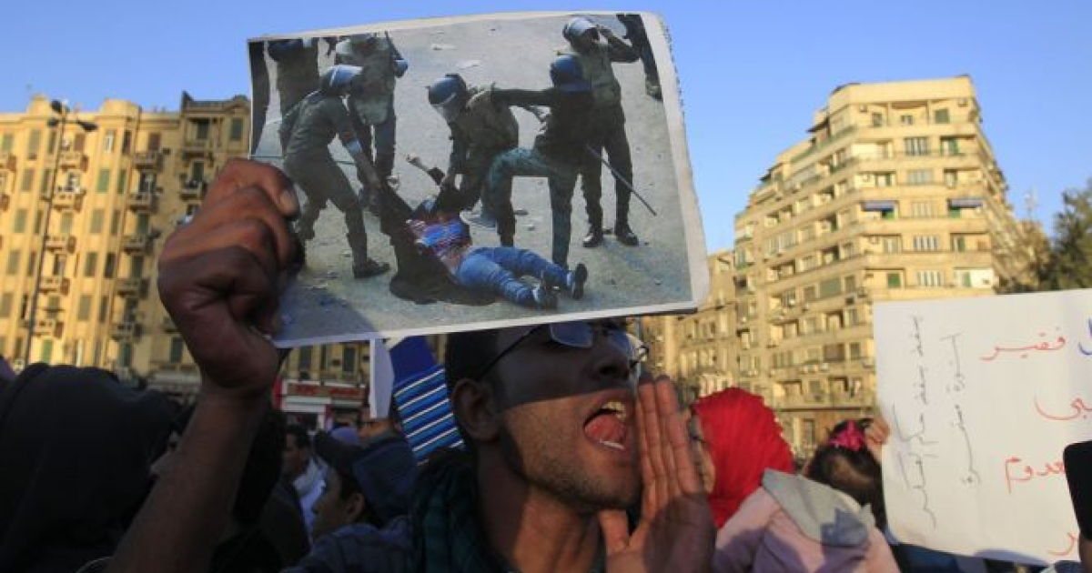 An Egyptian protester holds a modified version of the widely seen image of Egyptian troops beating a veiled woman after having ripped her clothes off to reveal her bra and stomach during recent clashes, at a demonstration against the military rule in Cairo's Tahrir Square on December 22, 2011.</p>