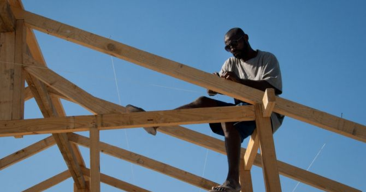 A man works to build a church roof using locally purchased, foreign-imported wood in the Neret neighborhood of Port-au-Prince.</p>
