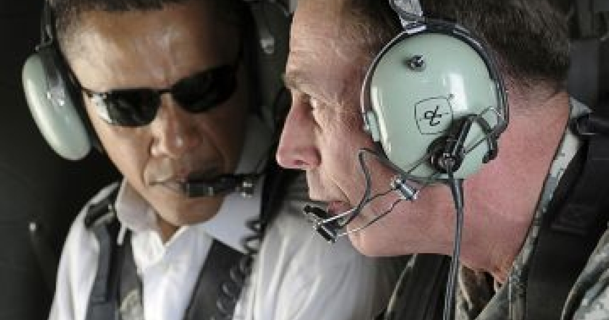Then U.S. Senator Barack Obama listens (left) as Gen. David Petraeus (right) discusses security improvements in Baghdad while giving him an aerial tour of the city, in this July 21, 2008 file photo. </p>