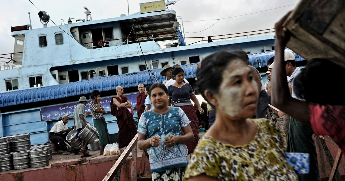 Passengers step off a boat docked at a jetty in Bogalay, Myanmar.</p>