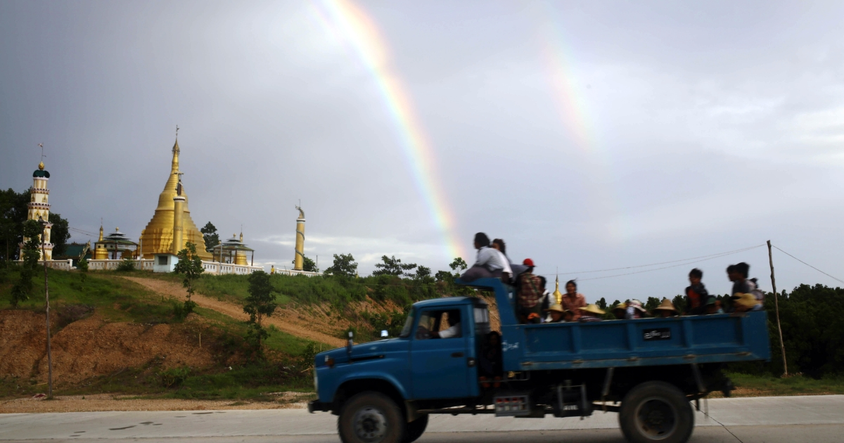 A truck carrying construction workers drives past a hill in Naypyidaw, Myanmar.</p>