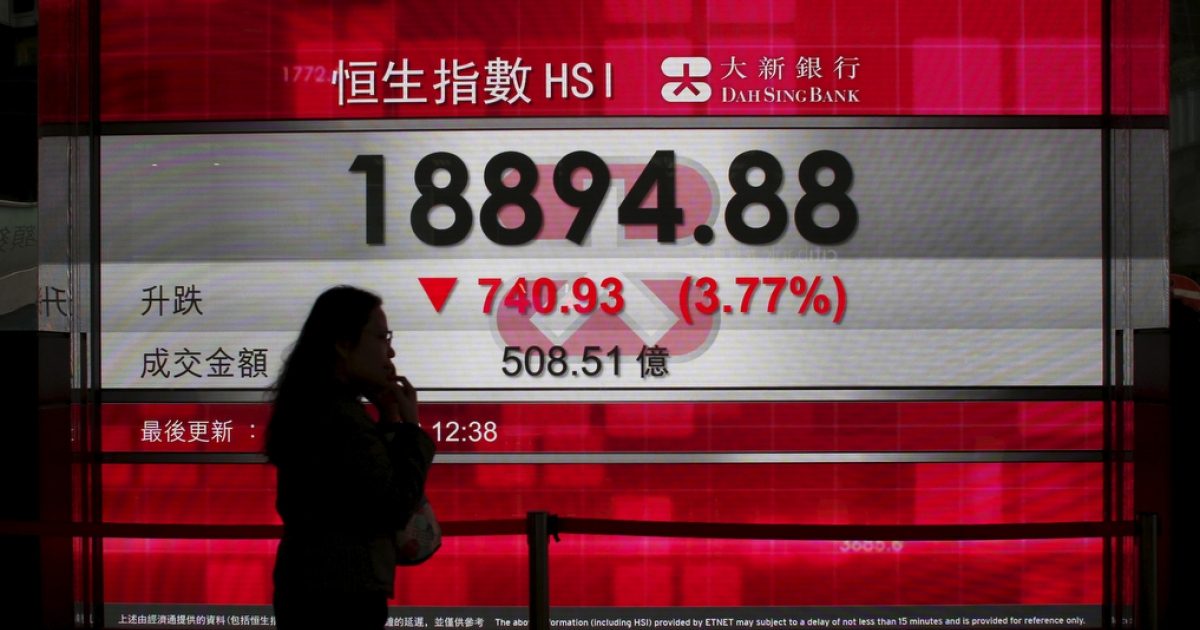 A woman talking on a cell phone walks past a panel displaying the midday Hang Seng Index in Hong Kong on Jan. 20, 2016.