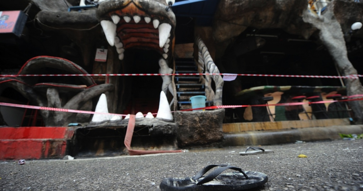 A flip-flop lies on the ground in front of the burnt remains of the Tiger nightclub in Phuket on August 17, 2012.</p>