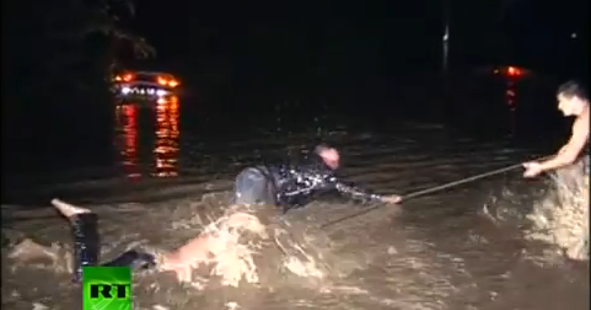 This still from a YouTube video shows men being dragged from the floodwaters with a rope.</p>