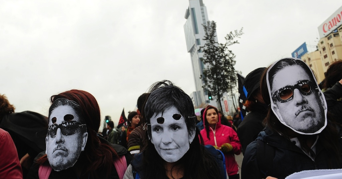 Students wearing masks of late dictator Augusto Pinochet and deputy Carolina Toha (C), demonstrate to demand that President Sebastian Pinera's government overhaul the education system to guarantee free, quality public education for all Chileans, in front of La Moneda presidential palace in Santiago on June 28, 2012.</p>