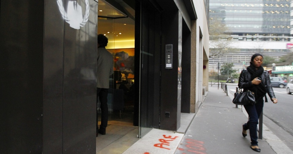 A woman walks past a graffiti made by the shadowy online hackers group Anonymous at the entrance of the French anti-piracy watchdog Hadopi headquarters on January 30, 2012 in Paris.</p>