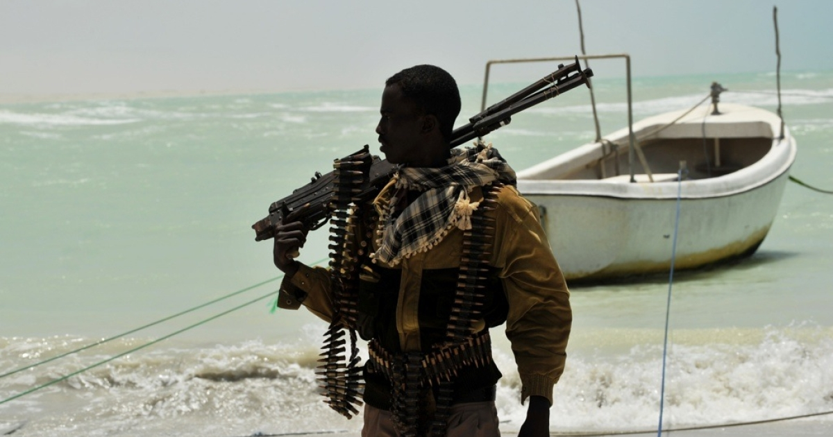 A Somali pirate carries his high-caliber weapon on a beach in the central Somali town of Hobyo on August 20, 2010.</p>