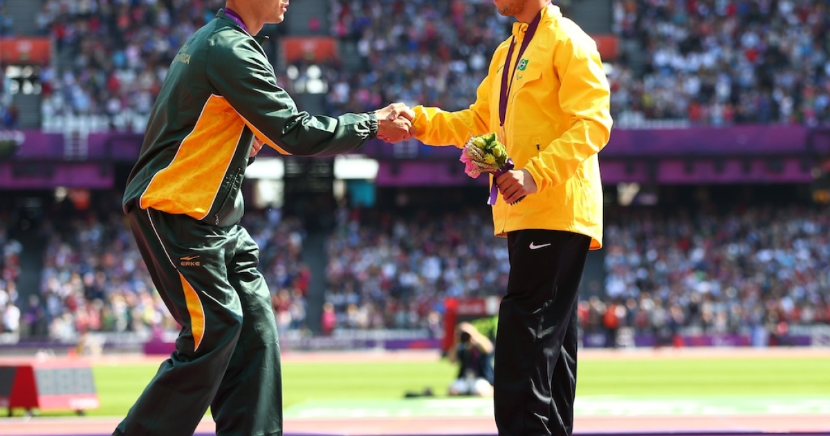 Silver medalist Oscar Pistorius of South Africa shakes hands with the gold medalist Alan Fonteles Cardoso Oliveira on the podium during the medal ceremony for the Men's 200m - T44 on day 5 of the London 2012 Paralympic Games at Olympic Stadium on September 3, 2012 in London, England.</p>