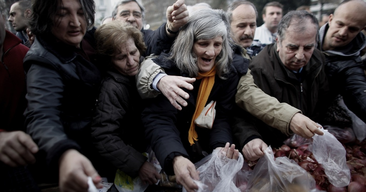 People grab free produce distributed by farmers on January 25, 2012 in Athens. Jurre Hermans, a eleven-year-old boy from the Netherlands, uses food as a metaphor for his solution to the crisis. His proposal received honorable mention for the Wolfson Economics Prize.</p>