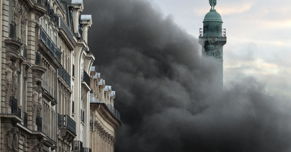 A cloud of black smoke envelops the Place Vendôme column, on March 8, 2012 in Paris, after a fire - which appears to have started in the nearby Hotel Ritz underground parking lot - broke out.</p>