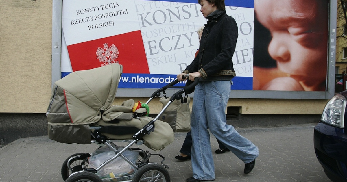 A mother with a child ispasses a poster with inscription 'Right to be born for every child' in Warsaw March 15, 2007. In 2007, Poland's Roman Catholic bishops  backed efforts by a far-right governing party to get the country's tough abortion law anchored in the constitution.</p>