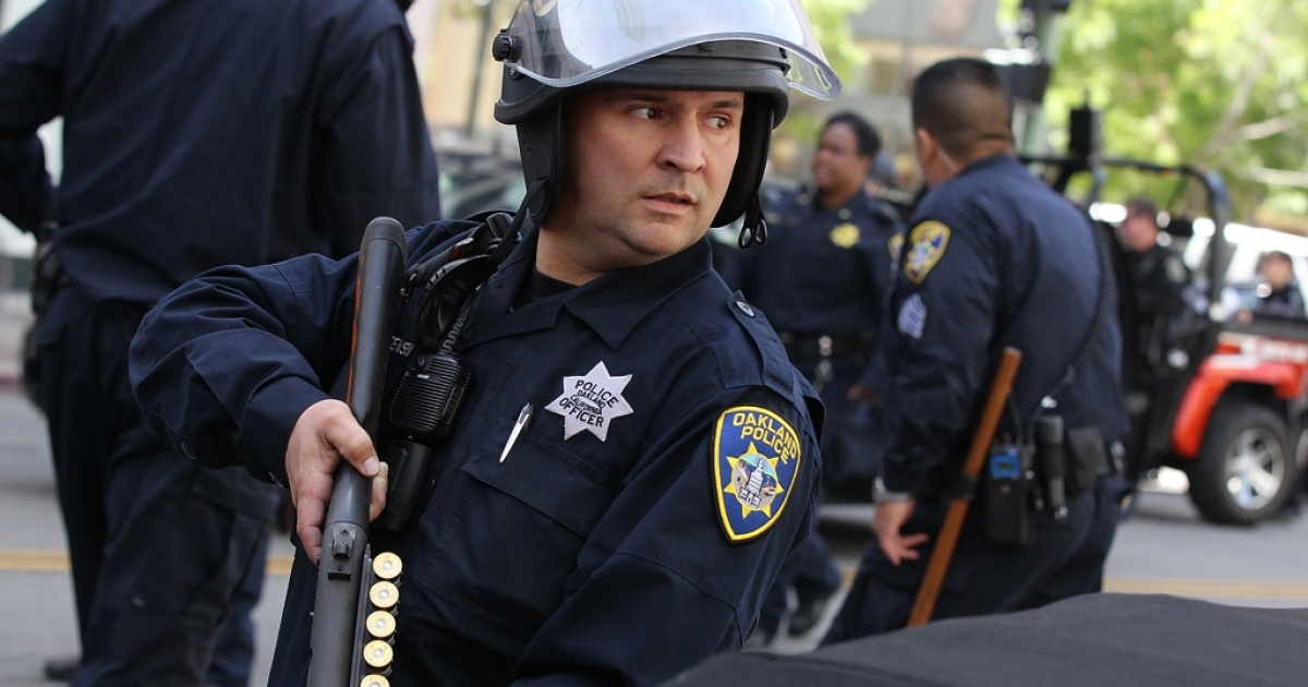 An Oakland police officer holds a shotgun as Occupy protesters are detained for attempting to block a street in Oakland, Calif., on May 1, 2012.</p>