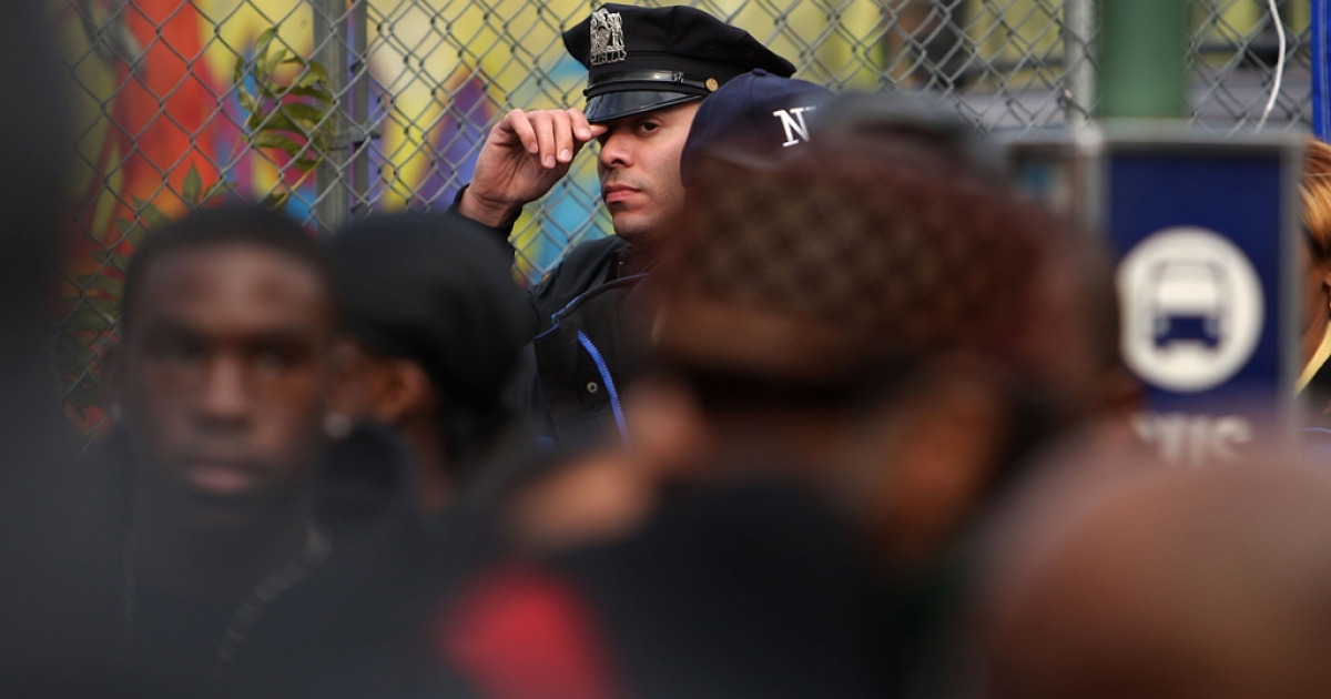 A police officer stands with residents near the spot where a youth was shot and killed by a policeman in Brooklyn, New York. The 911 calls related to the shooting of 17-year-old Trayvon Martin have sparked national outrage.</p>