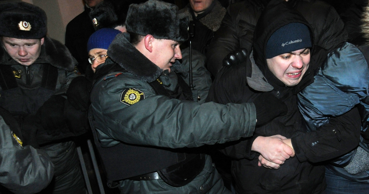 Police officers detain an activist in front of the Russian Central Election Commission headquarters in Moscow on Feb. 14, 2012, as a group attempted to hold an unauthorized protest.</p>