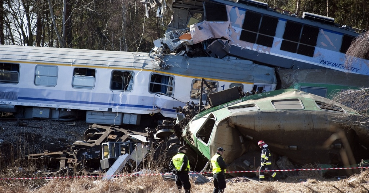 Policemen stand by the wreckage of two trains near the town of Szczekociny in southern Poland. The cause of the crash has yet to be determined.</p>