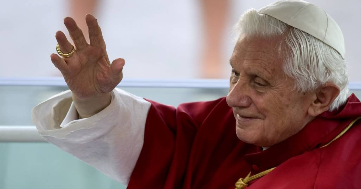 Pope Benedict XVI waves to faithful as he leaves the Almudena Cathedral in his popemobile after celebrating a mass during the World Youth Day festivities in Madrid.</p>