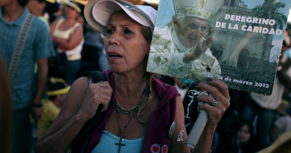 A woman waits for the arrival of Pope Benedict XVI for his mass at Havana's Revolution Square on the last day of his three day visit on March 28, 2012 in Havana, Cuba. Fourteen years after Pope John Paul II visited Cuba, Pope Benedict is making his first trip to the communist country.</p>