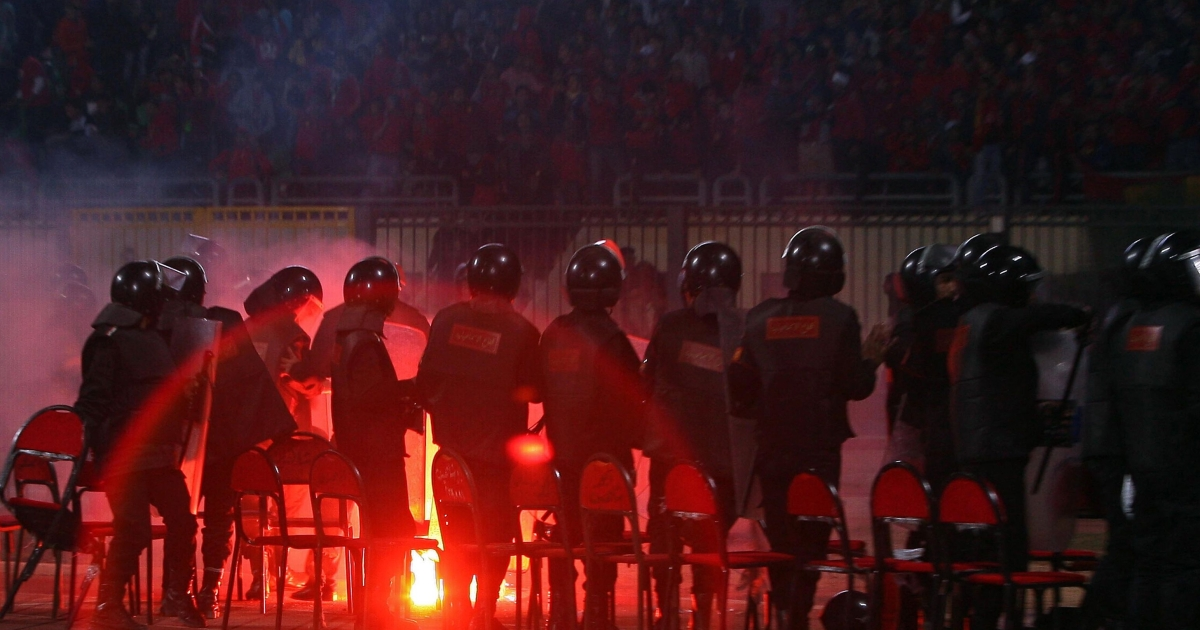 Egyptian riot policemen stand guard as a flare is thrown during a football match between al-Masry and al-Ahly in Port Said on February 1, 2012.</p>