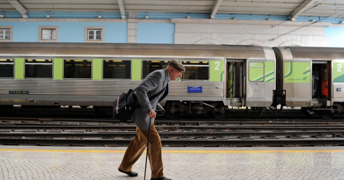 An elderly man walks to his train at the Santa Apolonia train station in Lisbon, on March 28, 2011.</p>
