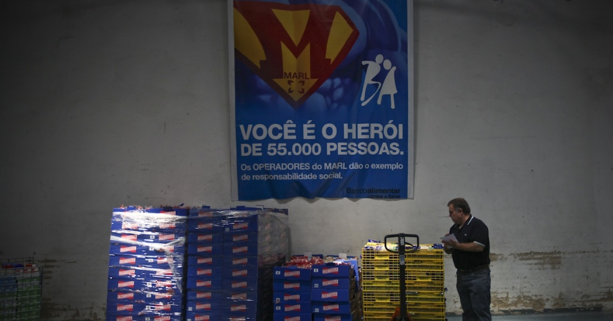 A volunteer loads food to give to charity institutions, in Lisbon on May 31, 2011. Like Spain, growing ranks of the hungry in Portugal continue to increase. Many rely on charities to survive.</p>