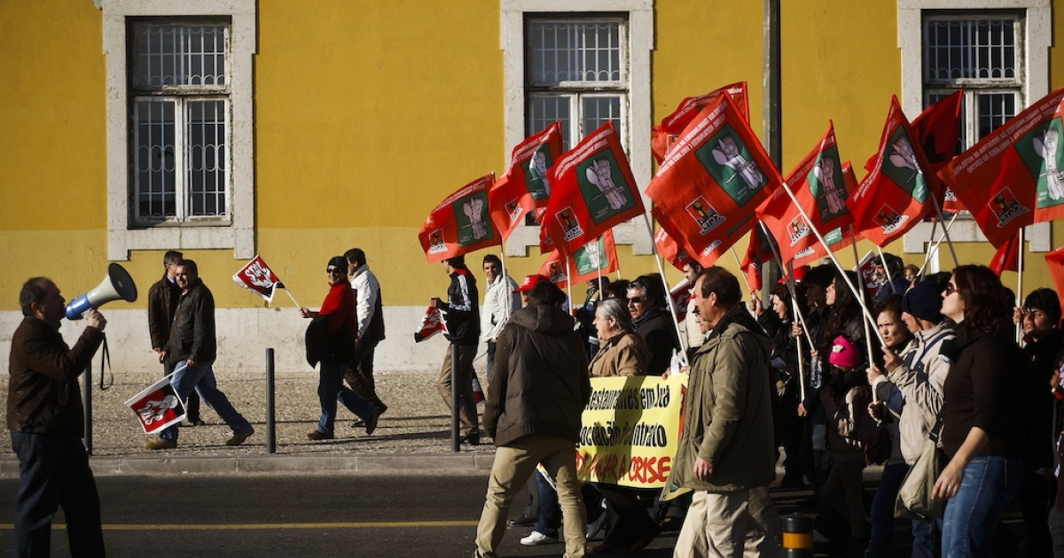 Workers wave flags and march in front of the Finance Ministry to reach Terreiro do Paco Square to protest against government austerity measures during a demonstration launched by Portugal's biggest trade union, Portuguese General Workers Confederation (CGTP), in Lisbon on February 11, 2012.</p>