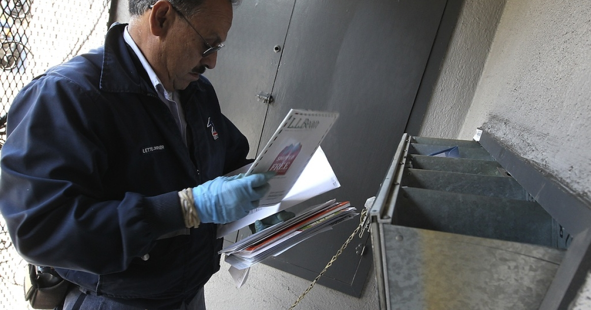 US Postal Service letter carrier Juan Padilla puts letters into a mailbox as he walks his delivery route on Dec. 5, 2011, in San Francisco, Calif.</p>