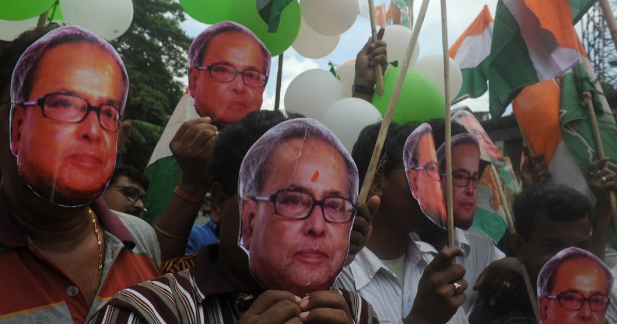 Activists of India's ruling Congress party wear face masks of India's new President Pranab Mukherjee as they celebrate his coronation in Kolkata on July 25, 2012.</p>